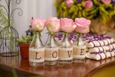 33- A mesa de lembrancinhas tem garrafas decoradas e completam a decoração de noivado. Fonte: Royal Convites