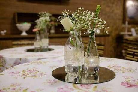 43- Espelhos redondos com garrafas transparentes e flores é a decoração de noivado nos centros das mesas. Fonte: Felipe Vieira Fotografia