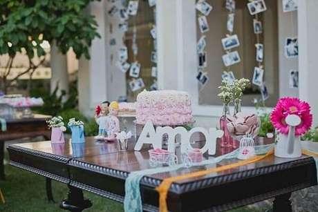 65- Na decoração de noivado o mural de fotos ganha destaque próximo à mesa de doces. Fonte: Canal da Decoração