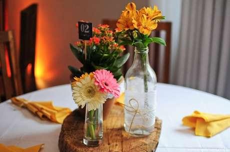 60- A decoração de noivado simples utiliza como centro de mesa garrafas com flores. Fonte: Casando Sem Grana