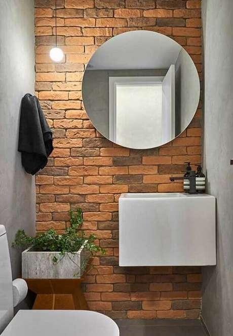 42. Pia para banheiro pequeno decorado com parede de tijolinho e espelho redondo – Foto: Apartment Therapy