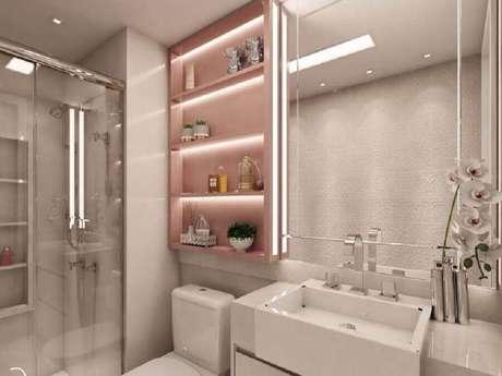 55. Delicada decoração com pia pequena para banheiro branco com nichos cor de rosa – Foto: Camila Fleck