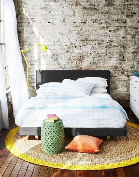 4. Decoração rústica com estilo industrial para decoração de quarto com tapete redondo embaixo da cama e parede de tijolinho – Foto: Style By Freedom