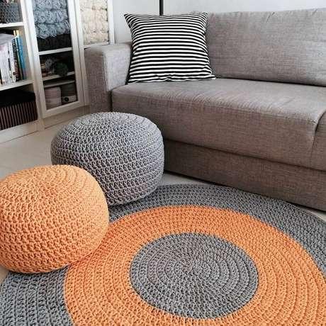 17. Decoração com puff e tapete redondo de crochê para sala de estar cinza com detalhes em laranja – Foto: Anne Kaz