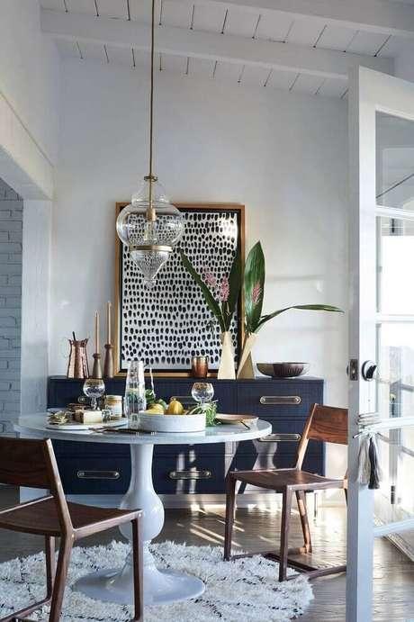 29. Decoração com tapete redondo para sala de jantar com mesa branca e buffet azul marinho – Foto: Kosova MGT