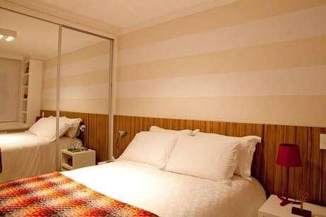 13. Decoração em tons neutros para quarto de casal com papel de parede listrado e cabeceira de madeira – Foto: Gabriela Marques