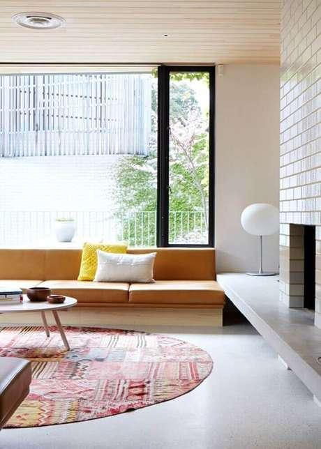 39. Decoração moderna para sala de estar com parede de tijolinho e tapete redondo estampado – Foto: Pinterest