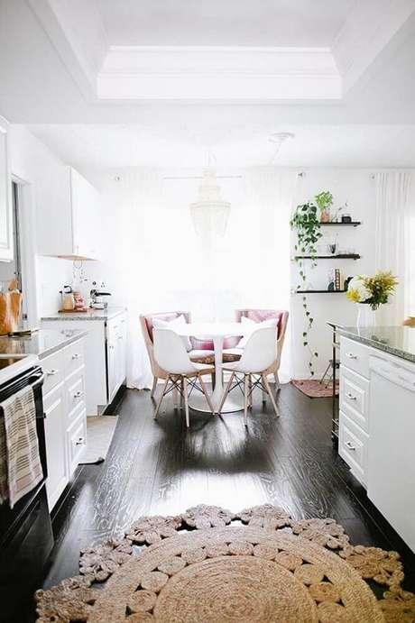 40. O tapete redondo de barbante ganhou bastante destaque na decoração da cozinha com piso de madeira escuro – Foto: Buk & Nola
