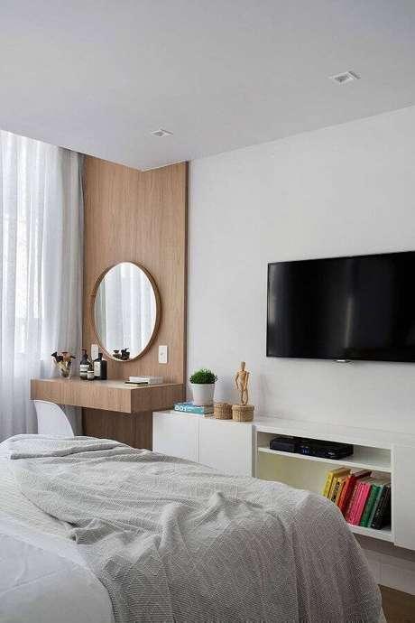 31. Modelos de quarto decorados com penteadeira suspensa e espelho redondo em revestimento de madeira – Foto: Conexão Decor