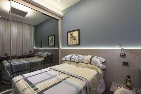 45. Decoração clean para quarto planejado com guarda roupa espelhado e iluminação embutida atrás da cama – Foto: Mariela Uzan