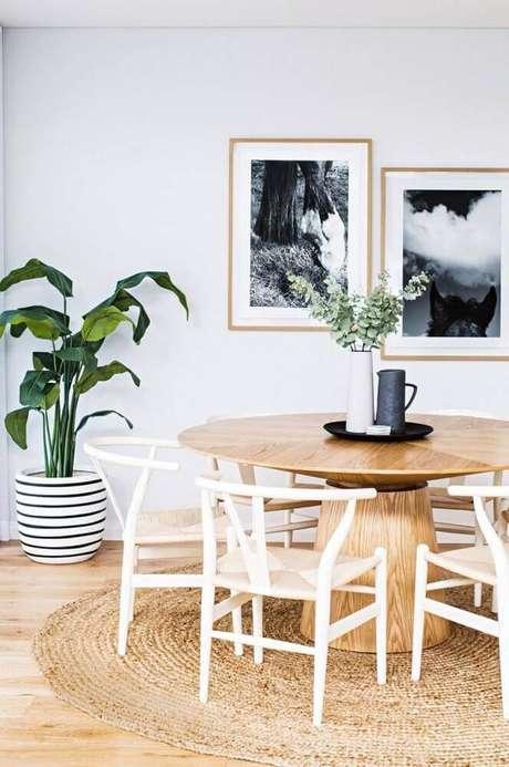 55. Decoração clean para sala de jantar com mesa redonda de madeira e tapete redondo de barbante – Foto: Casa&Diseño