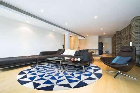 77. Sala de estar com tapete redondo geométrico e poltrona de couro preto – Projeto por By Kami
