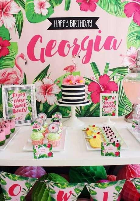 35. Decoração de festa flamingo com painel de folhagens e bolo listrado decorado com flores no topo – Foto: A Minha Festinha