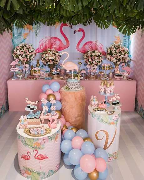 36. Decoração delicada para festa flamingo infantil azul e rosa com folhagens sobre a mesa do bolo e arranjo de rosas – Foto: Scotti Produções
