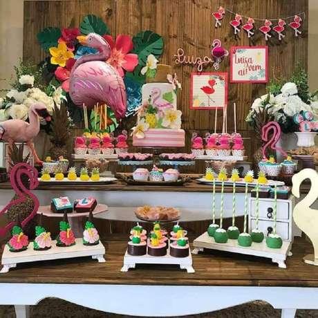 91. Mesa de festa de aniversário de flamingo decorada com doces personalizados e flamingos grandes – Foto: Rebeca Bassalo Festas