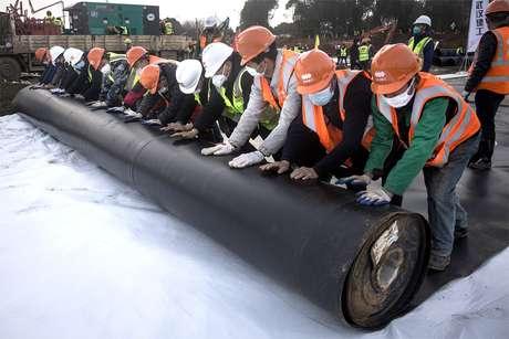 Operários da construção civil instalam revestimento à prova de umidade