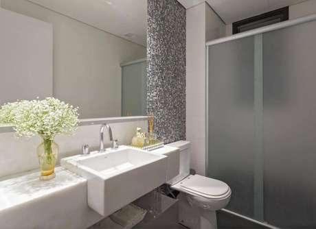 35. O modelo simples de espelho para banheiro tem o arremate das pastilhas de vidro. Projeto por Amis Arquitetura