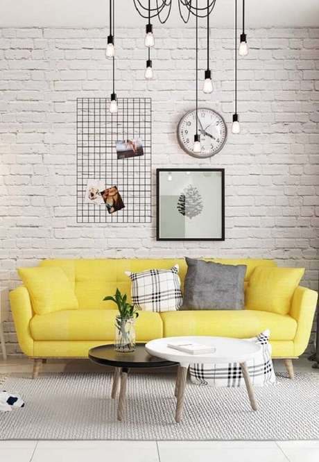 16. O sofá amarelo se destaca no ambiente com parede de tijolinho branco. Fonte: Pinterest