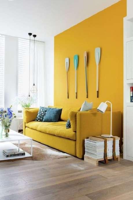12. A parede pode seguir a mesma tonalidade do sofá amarelo. Fonte: Simplichique