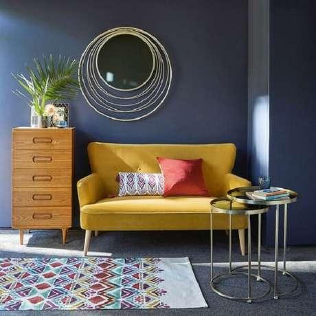 13. O sofá amarelo trouxe luminosidade para o cômodo com parede escura. Fonte: Pinterest