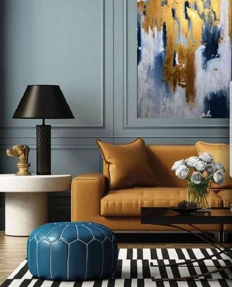 23. O sofá amarelo se harmoniza com o quadro abstrato da parede. Fonte: Boca de Lobo