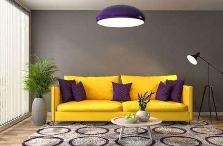 27. Sala de estar com sofá amarelo e almofadas roxas. Fonte: Pinterest