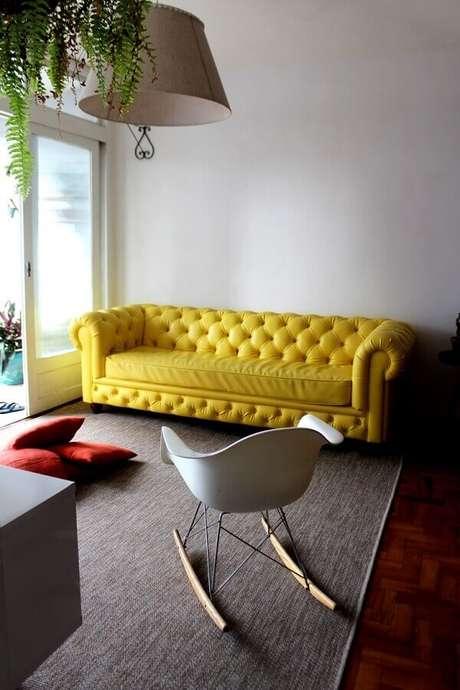 28. Sala de estar com sofá amarelo chesterfield e cadeira de balanço Eames branca. Fonte: Pinterest