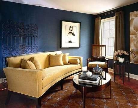 30. O sofá amarelo ilumina a sala de estar com paredes escuras. Fonte: Pinterest