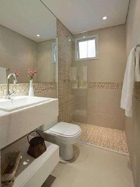 15. Cerâmica para banheiro com faixa de pastilha abaixo do espelho.