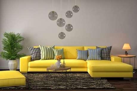 31. Modelo de sofá amarelo com chaise e almofadas listradas. Fonte: Pinterest