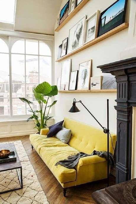 35. Sala de estar com sofá amarelo e prateleiras para quadros. Fonte: Pinterest