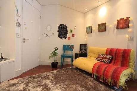 5. Quadros decorativos e sofá cama amarelo. Projeto por Caravieri Cardoso Arquitetura