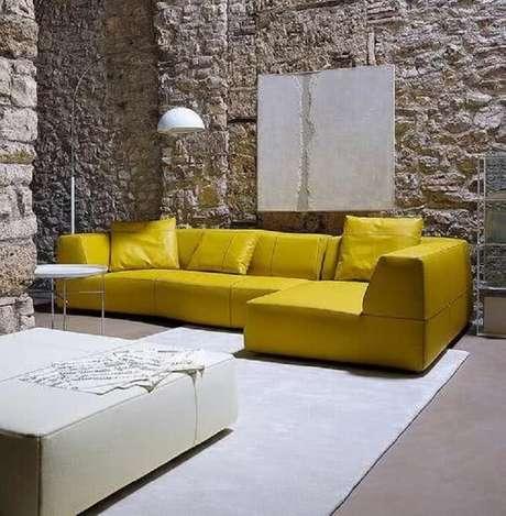 53. Sala de estar com parede de pedra e sofá amarelo de canto. Fonte: Pinterest