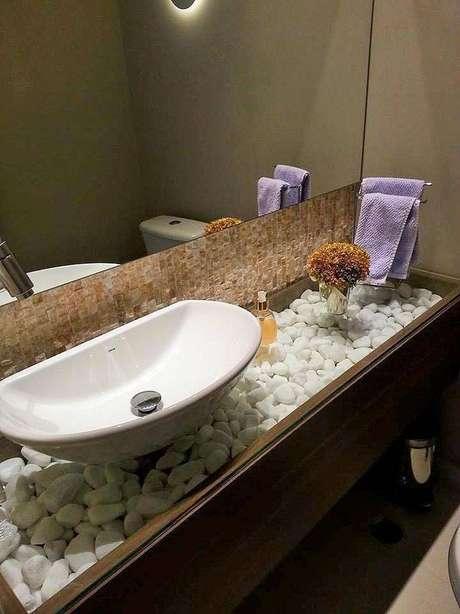 20.A cuba para banheiro combina perfeitamente com as pedras que decoram a bancada de vidro e madeira. Projeto por Alane Dias Pestana