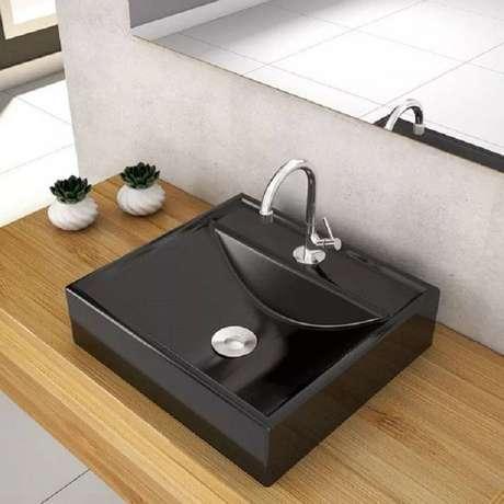 53. As cubas para banheiro quadrada em tons pretos foram colocadas sobre bancada de madeira. Fonte: Ana Spagnuolo & Marcos Ribeiro