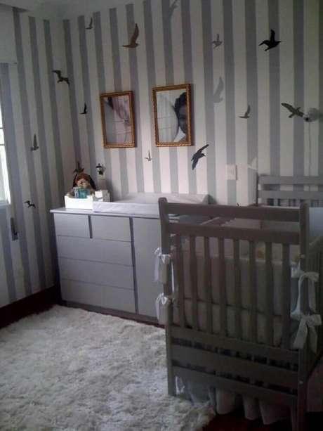 29. Quarto de bebê com decoração em tons de cinza e com papel de parede listrado com desenhos de pássaros