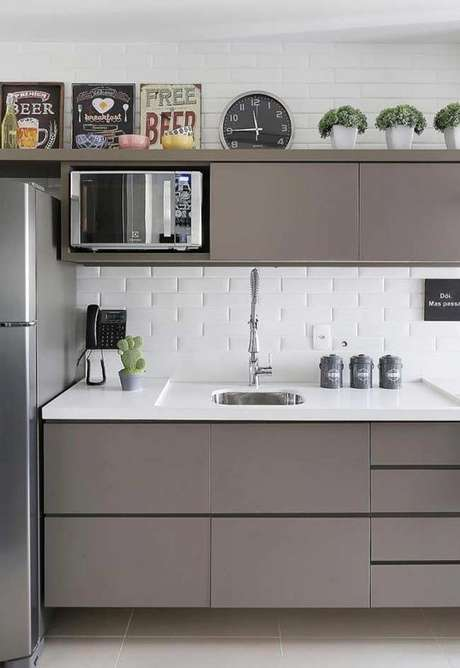 56. Armário de cozinha marrom com revestimento de tijolinhos – Foto: Ideias Decor