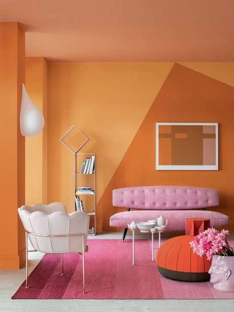 1. Sala de estar descontraída e alegra com parede laranja e tapete rosa. Fonte: Casa Abril