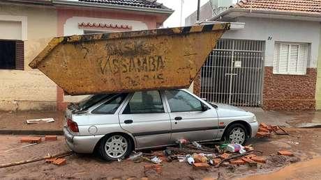 Com a força da correnteza, uma caçamba de aço foi parar sobre o capô de um carro, em Botucatu, interior de São Paulo.