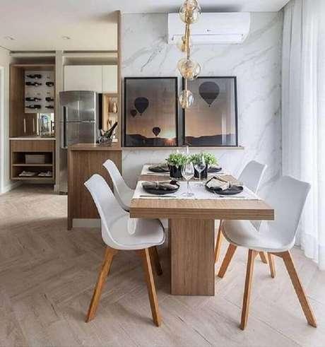 10. Sala de jantar moderna decorada com mármore para revestimento de parede e mesa com cadeira branca – Foto: Homedit
