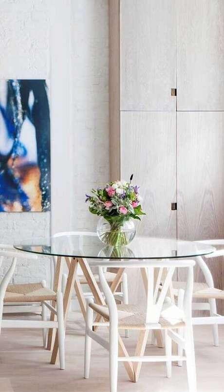 7. Decoração clean com mesa de vidro redonda e cadeira branca para sala de jantar – Foto: Pinterest
