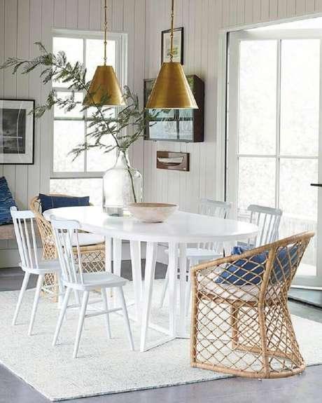 20. Sala de jantar decorada com mesa com cadeira branca e pendentes cobre – Foto: Serena & Lily