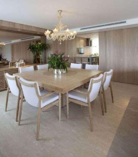 22. Cadeira de madeira branca para sala de jantar sofisticada com lustre candelabro e mesa quadrada – Foto: Planete-deco