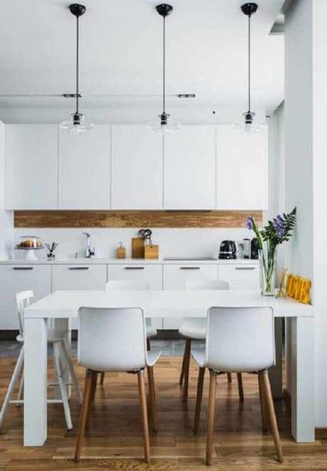 23. Cadeira de plástico branca com pernas de madeira para cozinha toda branca – Foto: Apartment Therapy