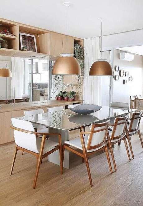 43. Decoração em tons neutros com cadeira de madeira branca para sala de jantar com mesa de vidro e pendente cobre – Foto: Ideas Decor