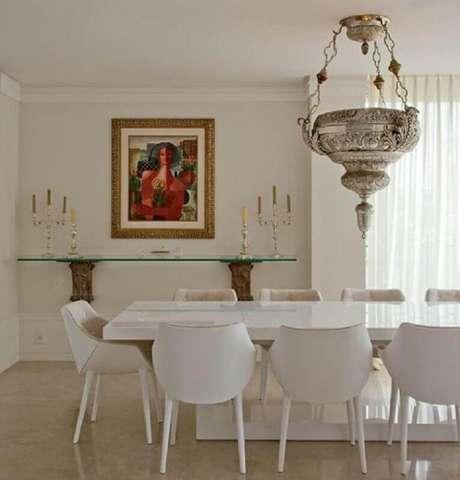 50. Decoração sofisticada para sala de jantar com mesa e cadeira branca e lustre grande de prata – Foto: Pinterest