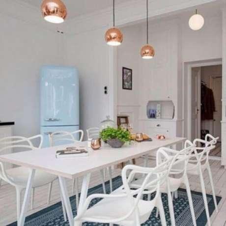 53. Mesa com cadeira branca para cozinha com pendentes rose gold e geladeira azul – Foto: Eduardo Cavalcanti Castro