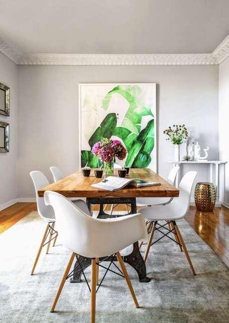 56. Mesa com cadeira branca eames para decoração de sala de jantar com tapete cinza e quadro grande – Foto: Pinterest