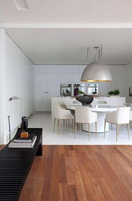 57. Mesa com cadeira branca estofada para decoração de sala de jantar moderna com pendente grande prata – Foto: Casa de Valentina
