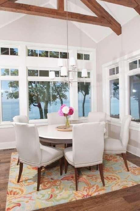 60. Mesa com cadeira branca para sala de jantar com amplas janelas e mesa redonda – Foto: House of Turquoise